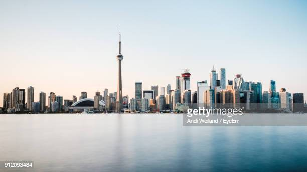 cn tower by lake against sky in city - toronto stock pictures, royalty-free photos & images