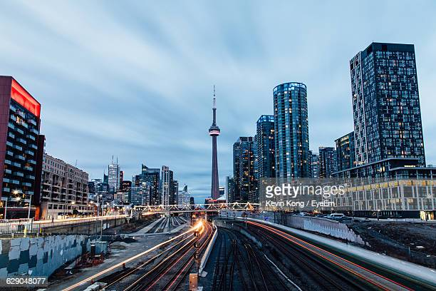 cn tower with cityscape against sky at dusk - toronto stock pictures, royalty-free photos & images