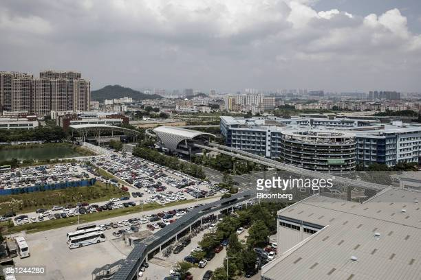 Co SkyRail monorail train stands at a station center as vehicles stand parked in a lot at the company's headquarters in Shenzhen China on Thursday...