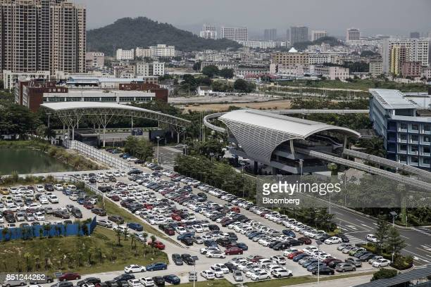 Co SkyRail monorail train stands at a station right as vehicles stand parked in a lot at the company's headquarters in Shenzhen China on Thursday...
