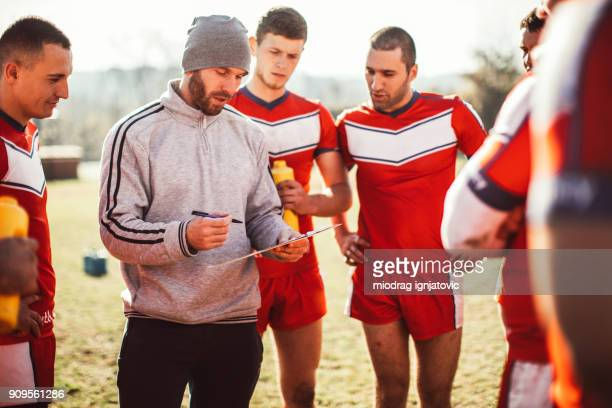 coach advising his team - sportkleding stock pictures, royalty-free photos & images