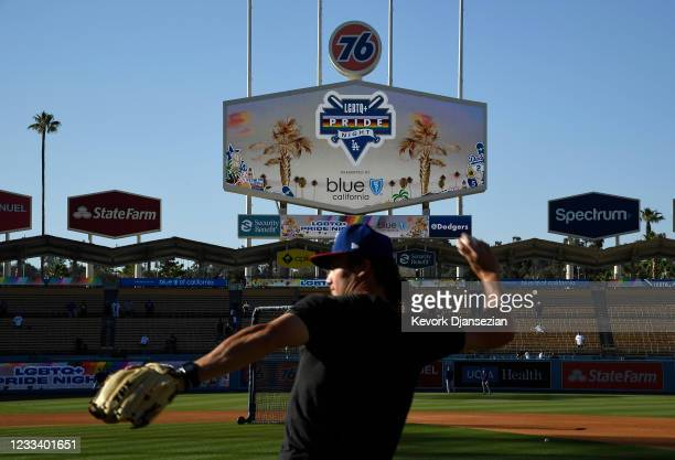 Coach Alex Burg of the Texas Rangers throws the baseball during eighth annual LGBTQ+ Night prior to start of a baseball game between the Los Angeles...