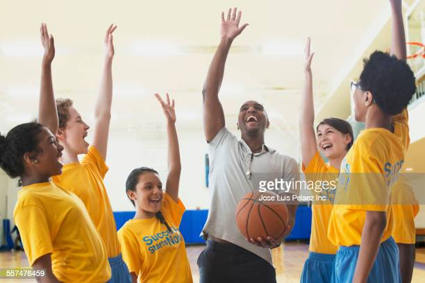 Coach and basketball team cheering during practice in gym