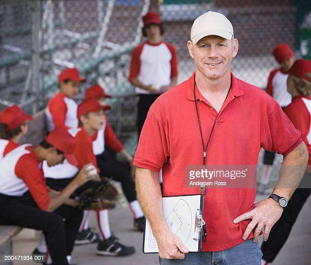 Coach and boys (9-11) in baseball dugout (focus on coach)