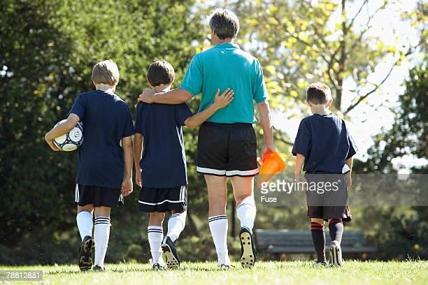 Coach and Boys Soccer Team Leaving Soccer Field