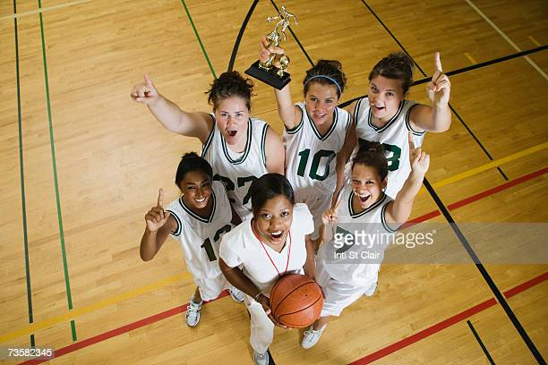 Coach and female basketball team celebrating, portrait, elevated view