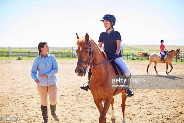 coach and girl on horse on riding ring - pferderitt stock-fotos und bilder