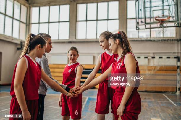 coach and girls basketball players holding hands - basketball team stock pictures, royalty-free photos & images