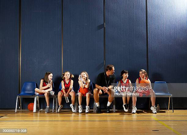Coach and girls (8-10) sitting on chairs beside basketball court