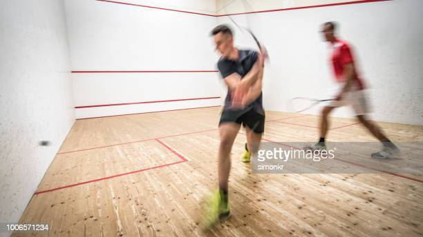 coach and his male student playing squash - squash sport stock pictures, royalty-free photos & images