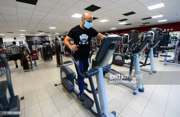Coach and manager of Body Staff Gym fitness centre Mabchour Mourad tests a machine on June 1 in ArtiguespresBordeaux southwestern France on the eve...