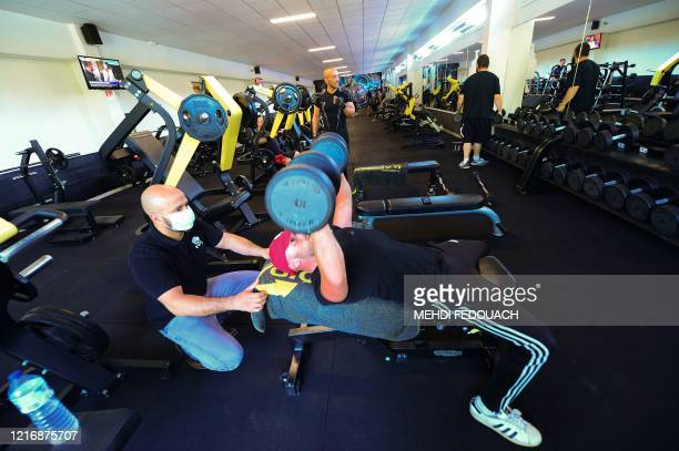 Coach and manager of Body Staff Gym fitness centre Mabchour Mourad wearing a protective facemask helps and gives instructions to a client on June 2...