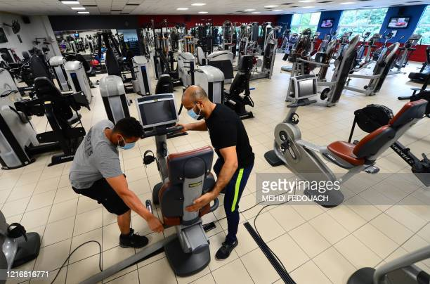 Coach and manager of Body Staff Gym fitness centre Mabchour Mourad places workout machines apart from each other for social distancing on June 1 in...