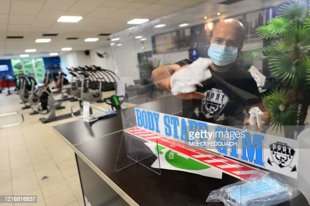 Coach and manager of Body Staff Gym fitness centre Mabchour Mourad sets up a plexiglass window at the front desk on June 1 in ArtiguespresBordeaux...