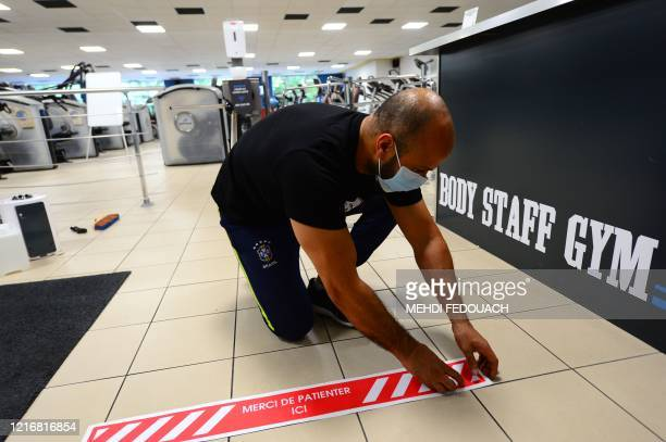 Coach and manager of Body Staff Gym fitness centre Mabchour Mourad sets up a social distancing marker at the front desk on June 1 in...
