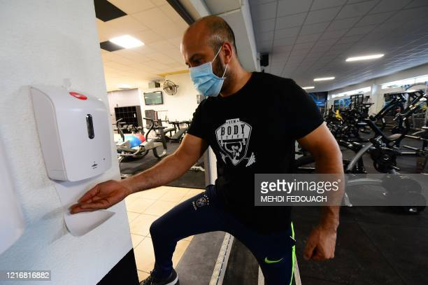 Coach and manager of Body Staff Gym fitness centre Mabchour Mourad sets up a hand sanitizer dispenser on June 1 in ArtiguespresBordeaux southwestern...