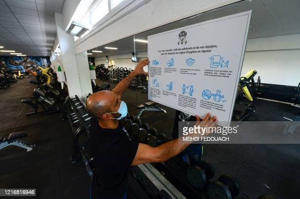 Coach and manager of Body Staff Gym fitness centre Mabchour Mourad sets up a safety measures information panel on June 1 in ArtiguespresBordeaux...