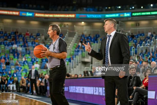 coach and referee standing with basketball - referee stock pictures, royalty-free photos & images
