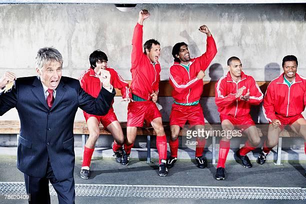 coach and soccer team on bench cheering - panchina delle riserve foto e immagini stock