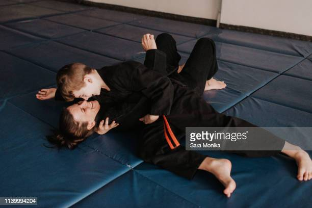 coach and student wrestling in studio - wrestling stock pictures, royalty-free photos & images