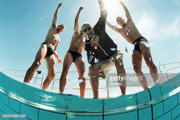 coach and swimmers cheering, portrait (wide angle, low angle view) - old man in speedo stock photos and pictures