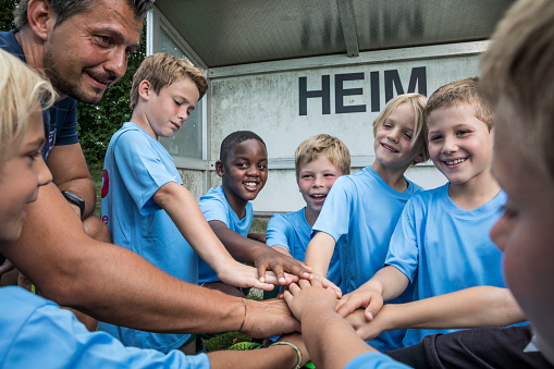 Coach and young football players huddling - gettyimageskorea