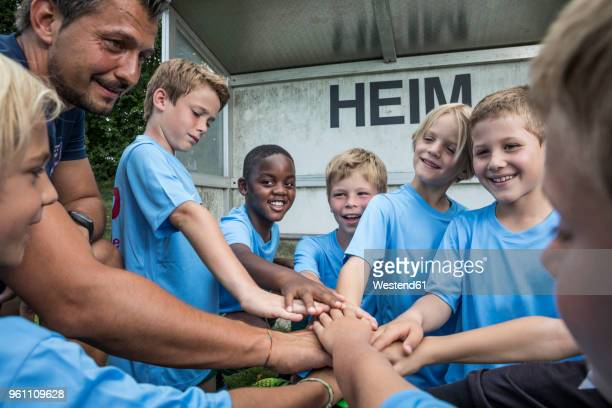 coach and young football players huddling - sportmannschaft stock-fotos und bilder