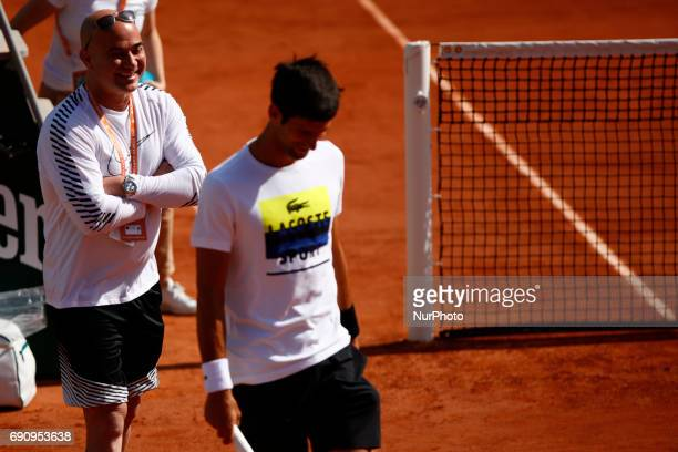 Coach Andre Agassi speaks with Novak Djokovic during a training session prior to his match against Joao Sousa on day four of the 2017 French Open at...