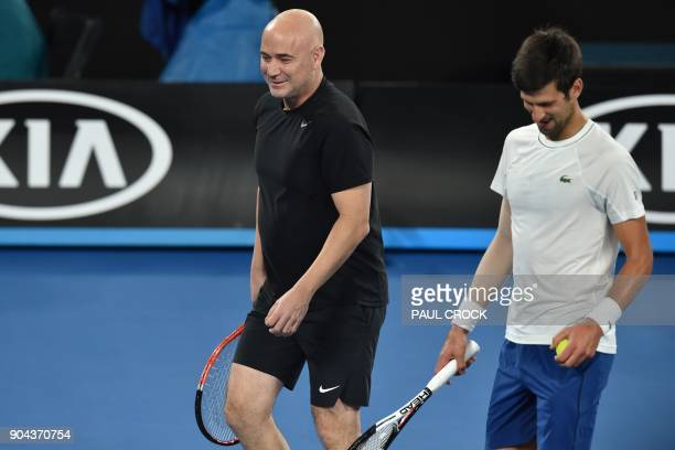 Coach Andre Agassi talks to Serbia's Novak Djokovic during a practice session ahead of the Australian Open tennis tournament in Melbourne on January...