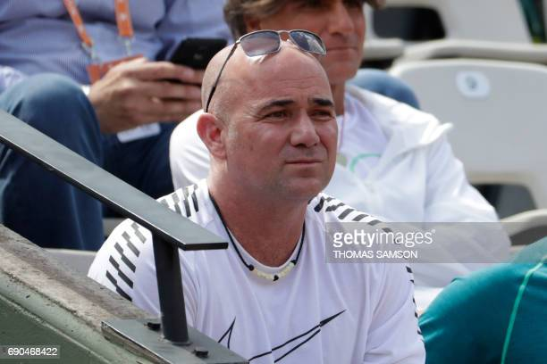 US coach Andre Agassi watches Serbia's Novak Djokovic playing against Portugal's Joao Sousa during their tennis match at the Roland Garros 2017...
