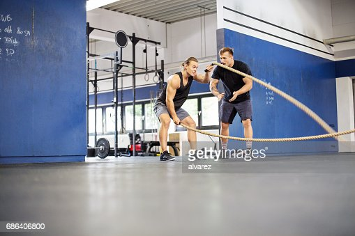 Coach applauding for man exercising with ropes