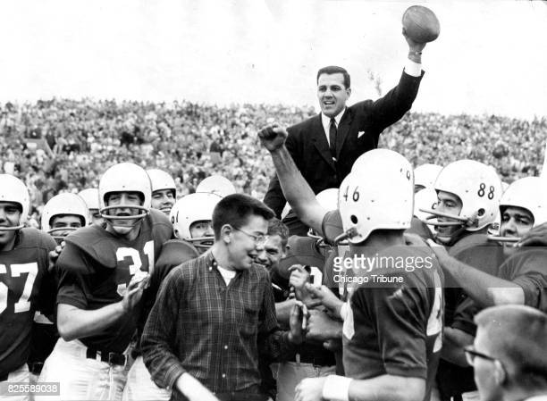 Coach Ara Parseghian salutes the Dyche stadium crowd with the game ball as his Northwestern Wildcats carry him off the field following their 210...