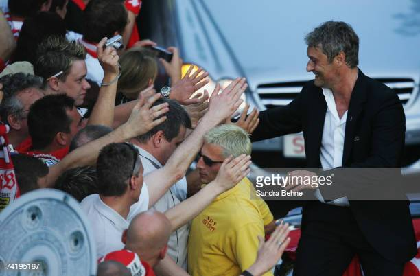 Coach Armin Veh of VfB Stuttgart shakes hands with fans during a car convoy after winning the German championships after the Bundesliga match against...