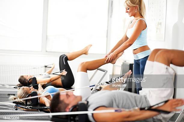 treinador assisiting a garota s'exercitar na máquina de pilates. - reformista - fotografias e filmes do acervo