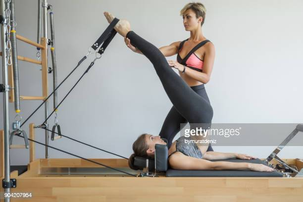 Coach assisiting the girl exercising on Pilates machine