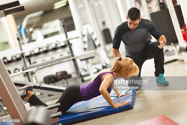 Coach assisting young woman doing push-ups  at a gym.
