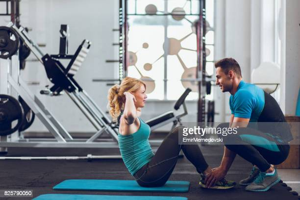 Coach assisting young woman doing sit-ups at a gym