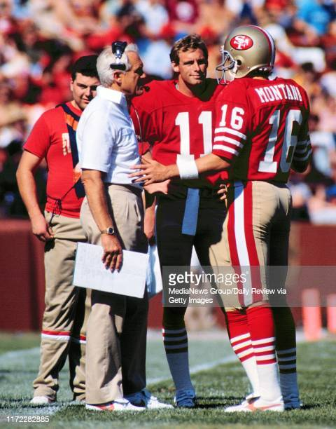 Coach Bill Walsh talks with Hall of Famer Joe Montana and replacement Quarterback Bob Gagliano in this strike game held on November 18 at Candlestick...