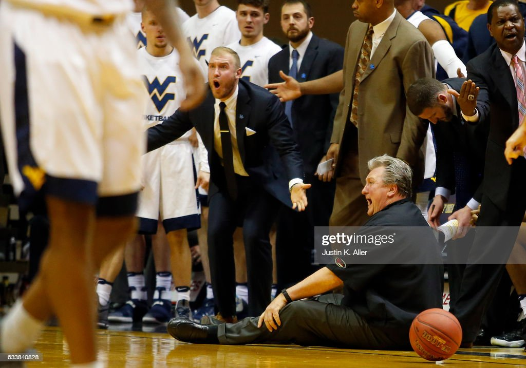 Coach Bob Huggins falls down arguing a call in the second half against the Oklahoma State Cowboys at the WVU Coliseum on February 4, 2017 in Morgantown, West Virginia.