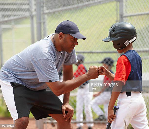coach bumping fists with little league batter - coach stock pictures, royalty-free photos & images