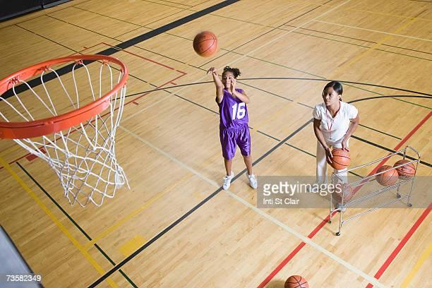 Coach by teenage girl (13-15) shooting basketball