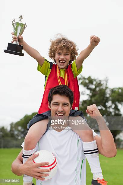 Coach carrying child with trophy