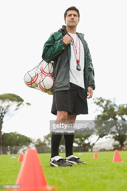 coach carrying soccer balls on pitch - trainer stock-fotos und bilder