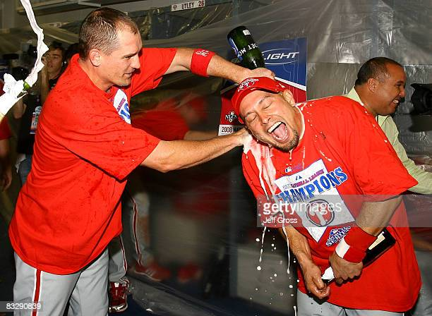 Coach Chris Coste and Shane Victorino of the Philadelphia Phillies celebrate in the locker room after winning Game Five of the National League...