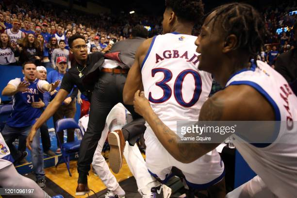 A coach comes between James Love III of the Kansas State Wildcats and Ochai Agbaji and Marcus Garrett of the Kansas Jayhawks during a brawl at the...