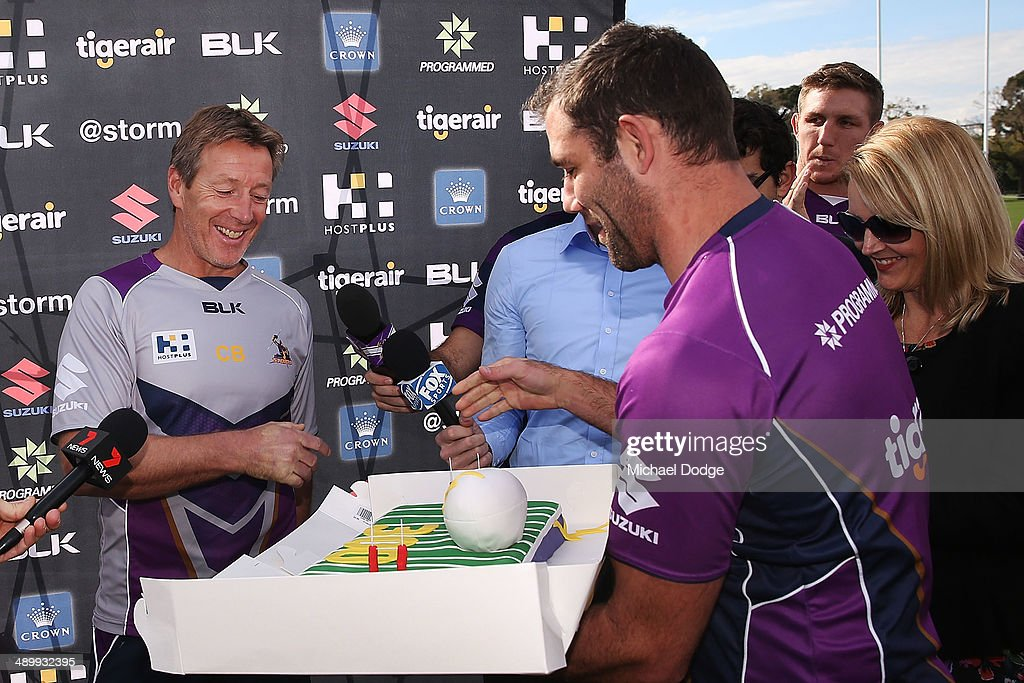 Coach Craig Bellamy reacts as Cameron Smith interupts to present him with a cake to celebrate his 300th game as Storm coach during a Melbourne Storm NRL media session at Gosch's Paddock on May 13, 2014 in Melbourne, Australia.