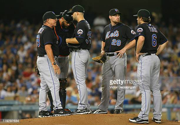 Coach Dan Warhen of the New York Mets visits the mound to talk to pitcher Dillon Gee as catcher Ronny Paulino Daniel Murphy and Nick Evans of the New...