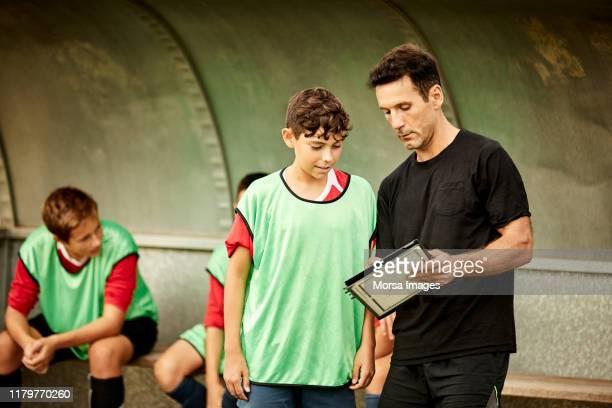 ônibus que discute a planta do jogo com jogador de futebol - treinador - fotografias e filmes do acervo