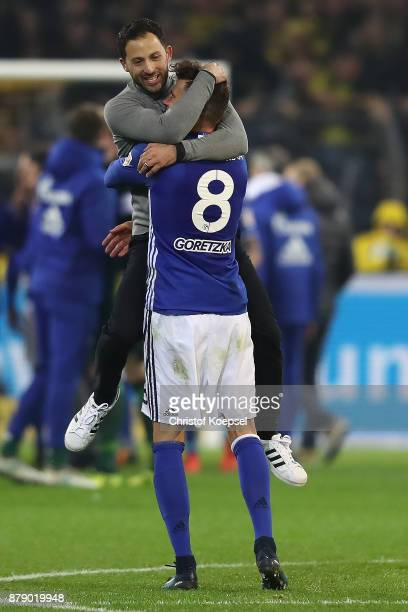 Coach Domenico Tedesco of Schalke celebrates with Leon Goretzka of Schalke after the Bundesliga match between Borussia Dortmund and FC Schalke 04 at...
