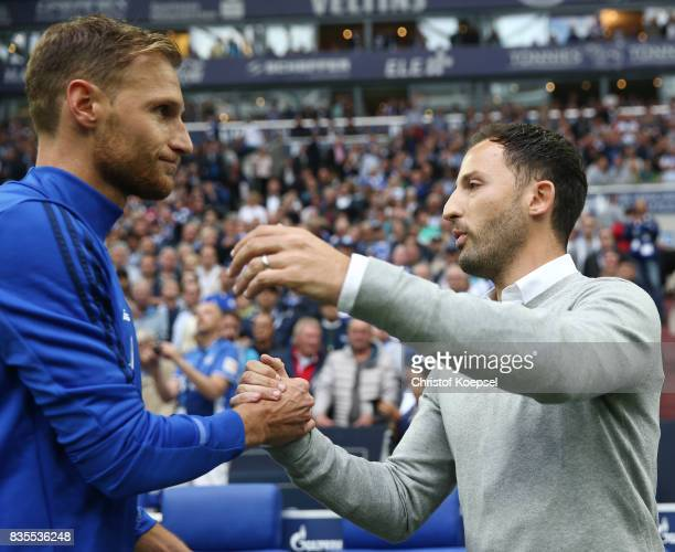 Coach Domenico Tedesco of Schalke shakes hands with Benedikt Hoewedes of Schalke during the Bundesliga match between FC Schalke 04 and RB Leipzig at...